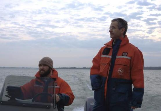 Two people in orange and blue float suits are on a boat. One is standing and the other sitting at the controls.