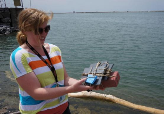 A person standing near the water holds up a brick with collection plates and a sponge tied to them