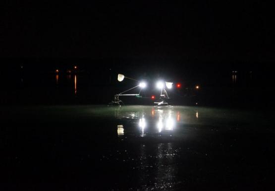Nighttime picture of a boat with headlights on the water
