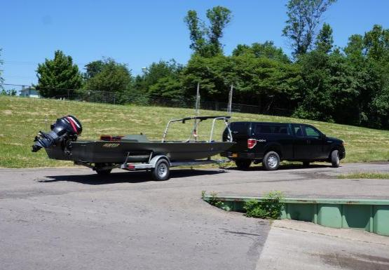 A truck and a boat on a trailer by a boat ramp.