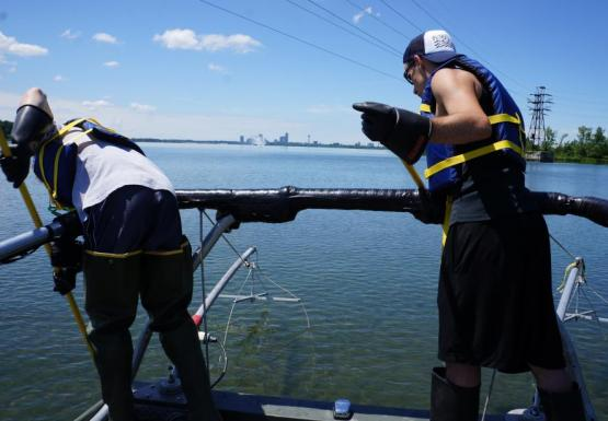 Two people lean over a railing at the front of a boat with long poles.
