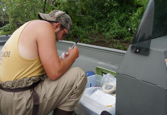 a person wearing chest waders kneels on a boat and writes information on a bottle
