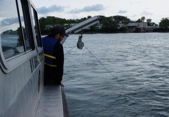A person near the edge of a boat looks toward a rope going into the water