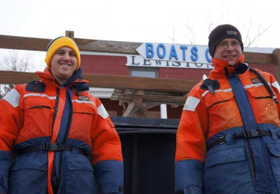 "two people in orange and blue float suits and knit caps stand in front of a building with a sign ""Boats"""