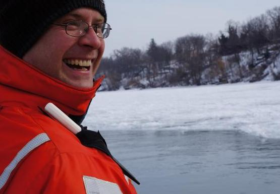 a person in an orange coat and knit cap smiles near the icy water