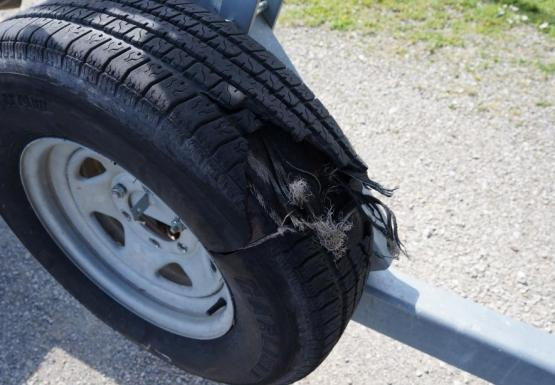 A tire that has blown open, secured to the frame of a boat trailer where the spare would normally go.