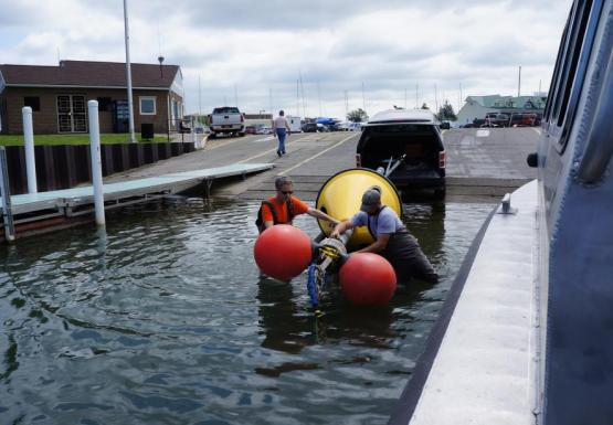 Two people wearing chest waders stand in shallow water to maneuver a buoy on a trailer. There are two floats tied to one end of the buoy.