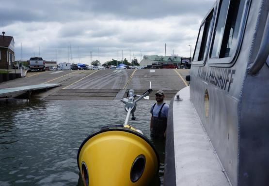 A person in chest waders stands in shallow water next to a buoy floating on its side next to a boat.