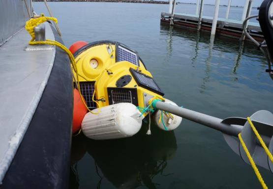 A buoy tied up alongside a boat. The buoy is lying on its side with numerous floats tied to it to keep it in position.