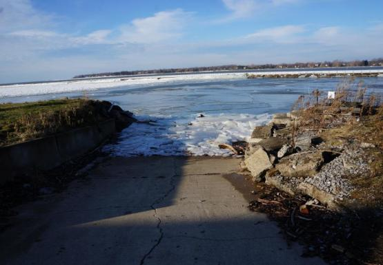 A boat ramp with ice piled about halfway up.