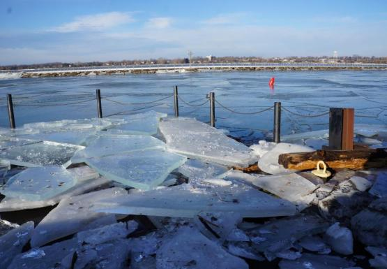 A boat dock covered with broken sheets of ice. The sheets of ice are at least 4 inches thick.