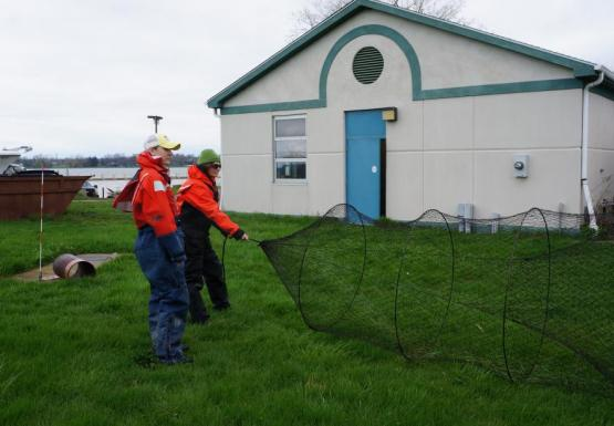 Two students in orange float suits hold a conical trap net open while standing on grass in front of a white building.