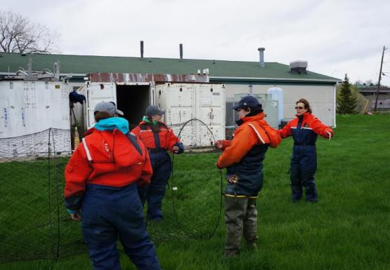 Three students in orange float suits hold a conical trap net open, while Dr. Alicia Pérez-Fuentetaja describes how it functions, during an on-land demonstration. The net opens up toward the right.