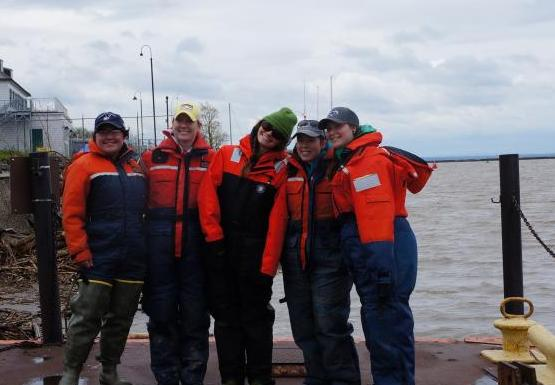 Five students from the fisheries class pose on the dock in their orange float suits.