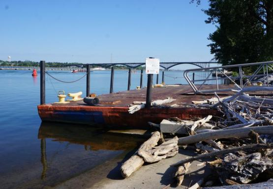 A dock made from a rusty sunken barge, painted orange. Piles of driftwood sit on the concrete next to the dock.