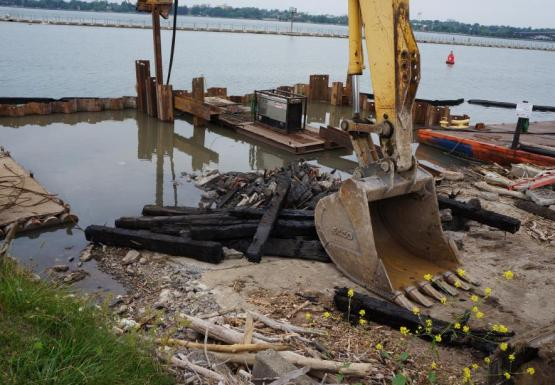 A construction zone at the edge of the water. There is a wall of steel surrounding the end of a boat ramp, which is full of water. At the end of the ramp are some blackened beams of wood. The bucket of an excavator rests on the ramp.