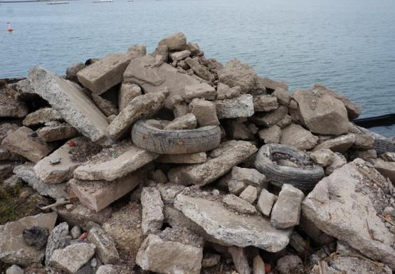 A pile of rocks, concrete debris, and tires by the waterfront.
