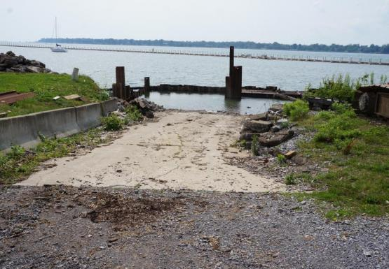 A boat ramp with a wall of steel beams surrounding the end of it. There is water on both sides of the wall.