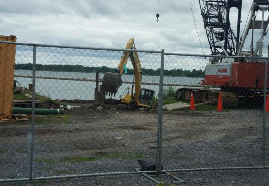 View of a construction site at the waterfront through a fence. An excavator is down near the water level and using a bucket to remove concrete from the boat ramp. There is also a crane sitting in the parking lot nearby.