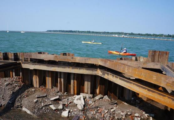Two kayakers paddle past a metal wall at the construction site. The water has been pumped out of the construction site, revealing mud and rubble below the waterline.