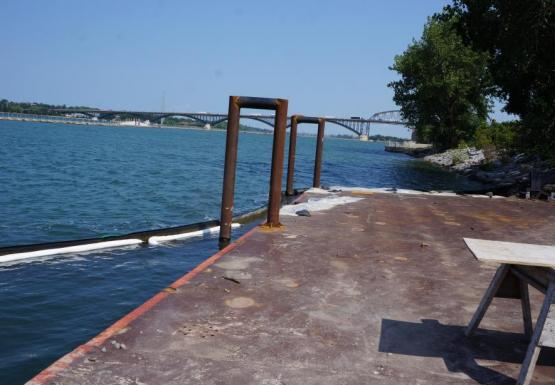 A metal surface by the water. Two U-shaped bars are attached to the side going into the water.
