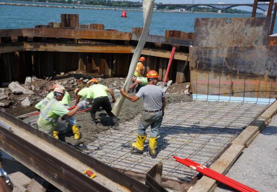 A construction crew working on laying cement on a frame. The construction area is bordered by a steel wall that holds out water.