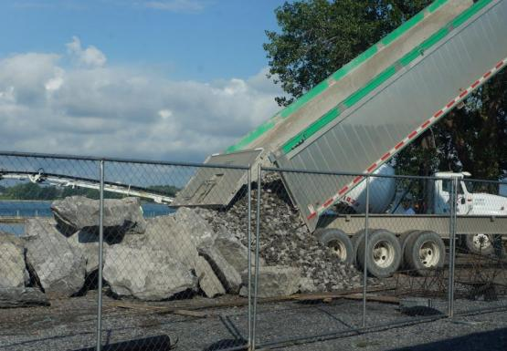 A dump truck pours out a load of small stone next to a pile of boulders.
