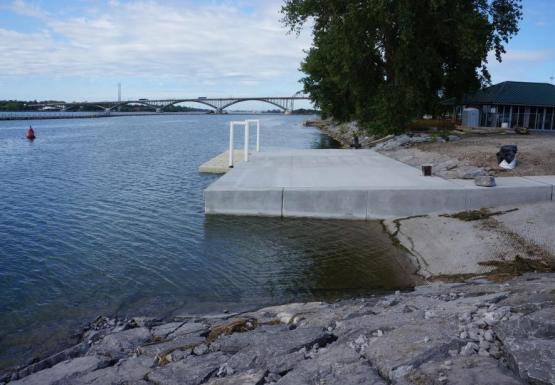 View of a boat launch and concrete dock with attached floating dock. Neat stones line the revetment in the foreground.