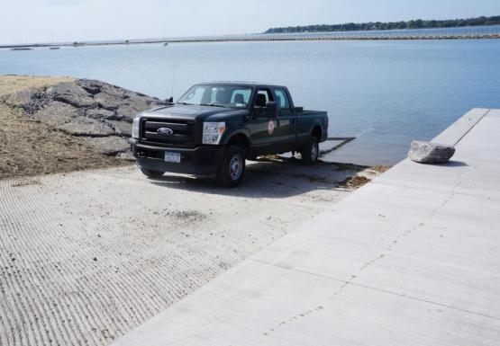 A pickup truck with a trailer backed into the water at a boat launch.