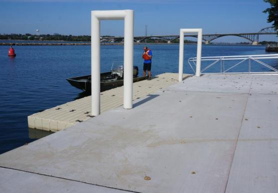 A person stands by a boat on a floating dock by the water. The main part of the dock is concrete and two white metal u-shaped bars connect to the floating dock.