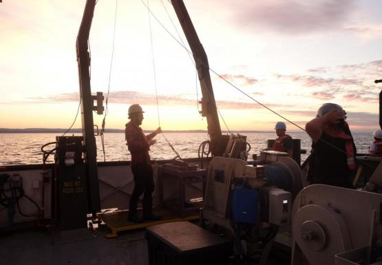 Three people working on the deck of a boat at sunrise or sunset