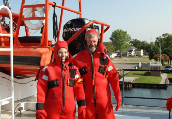 Two people wearing red survival suits on the deck of a large boat. There is an emergency rescue watercraft on deck behind them.