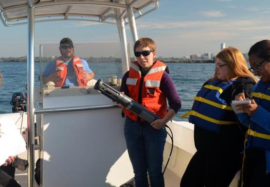 A class on a boat. One person stands at the control while another holds up a piece of equipment.