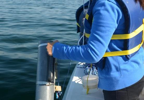 A different student stands by the edge of the boat, holding a grey cylinder over the water.