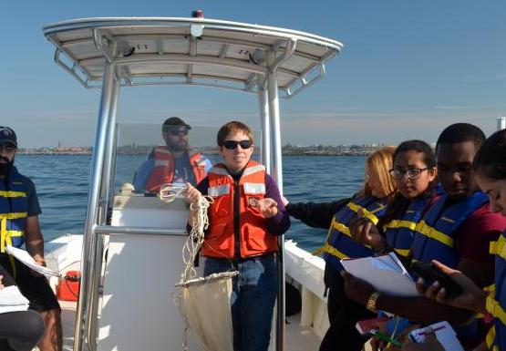 A class on a boat. One person stands at the control while another holds up a conical white net.