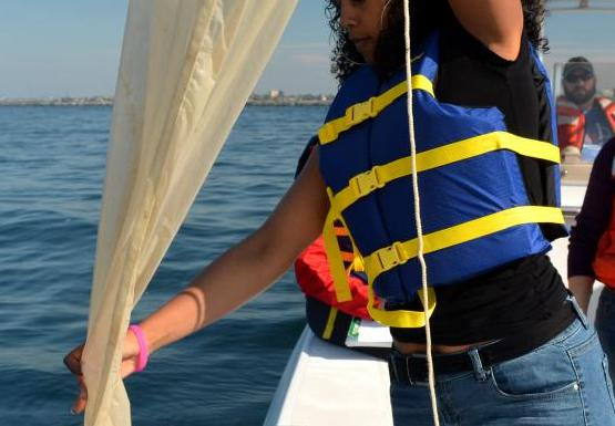 A student stands at the edge of a boat, pulling in a long white conical net.