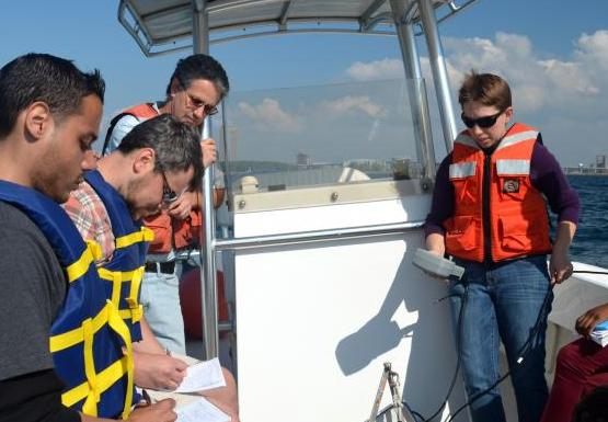 A class on a boat. A person looks at a grey instrument with a cable going into the water.