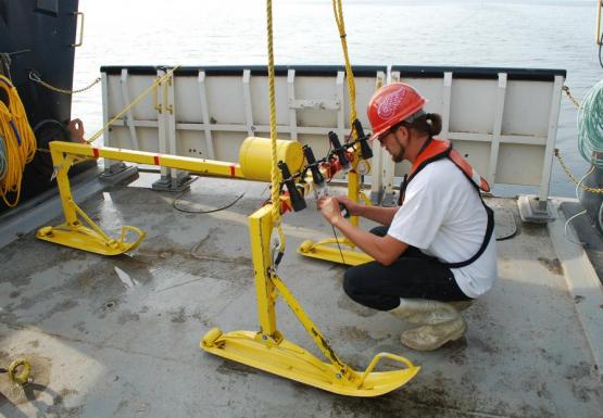 A person kneels before a metal frame with sled feet on the deck of a large boat. They are turning on lights and adjusting a camera.