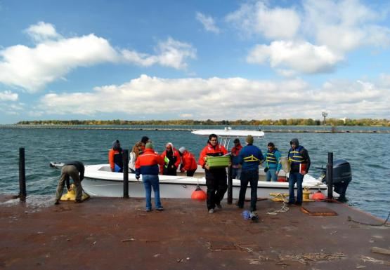 Several people on or near a boat at a dock. One is securing the boat with rope while some others carry supplies off the boat.