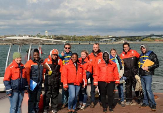 A portrait of a group of people wearing orange safety gear or life jackets, standing on a dock in front of a boat.