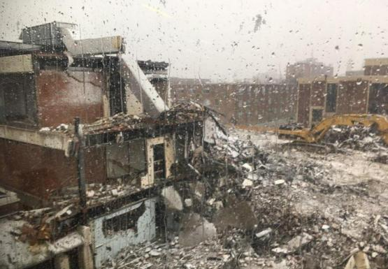 A construction site with a partially demolished three-story building with a light layer of snow covering the debris. The picture is taken through a window with water droplets on it.