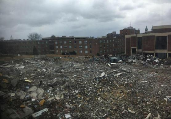 A field of rubble near some academic buildings.