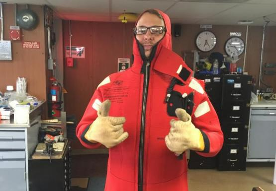 A person in a bright red safety gives two thumbs up inside a lab.