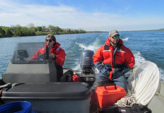 Two people sit at the back of a boat while one drives. There is a net next to one of them, and both are wearing orange safety suits.