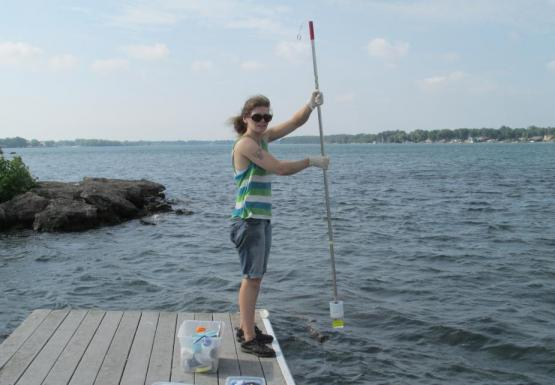 A person stands at the edge of a dock, holding a pole with a cup at the end of it.