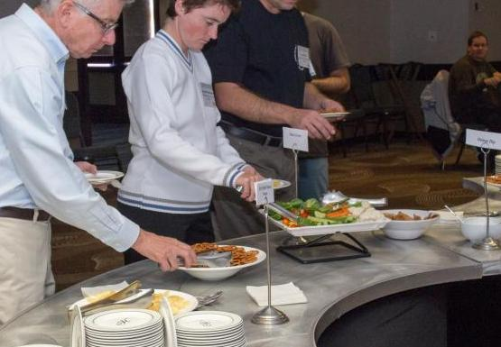 three people taking food from a buffet table