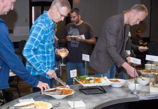 four people taking food from a buffet table