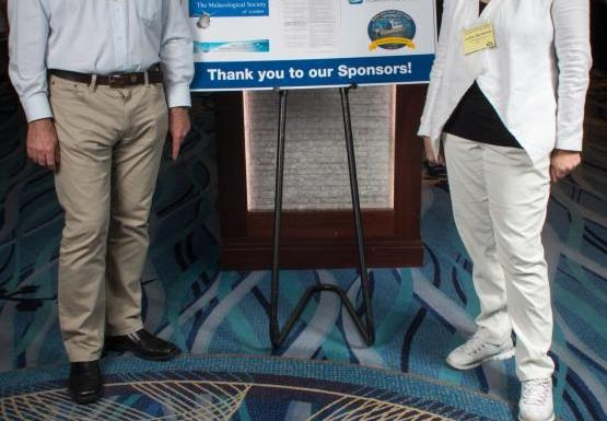 "two people stand on either side of a poster on an easel. The poster says ""thank you to our sponsors!"""