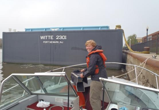 "A person stands on a boat tied to a wall near a freight vessel. The back of the large boat is labeled ""Witte 2301 Port Newark, NJ"""