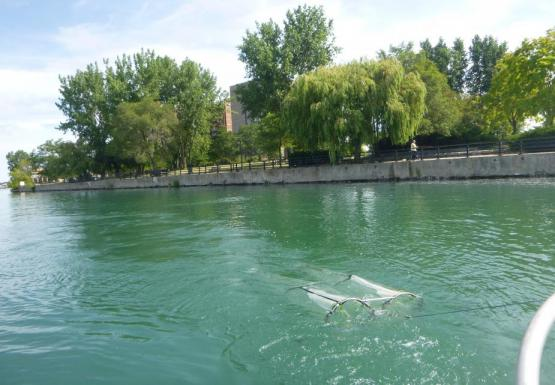 Two long round nets being towed through the water near the surface.
